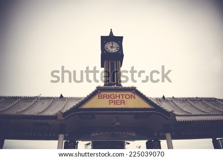 Exterior low angle view of the historical clocktower and sign for Brighton Pier at brighton, East Sussex, UK - stock photo
