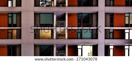 Exterior night view of apartment windows. Concept for anonymity, loneliness, alienation, modern life, lifestyle. Letterbox format - stock photo