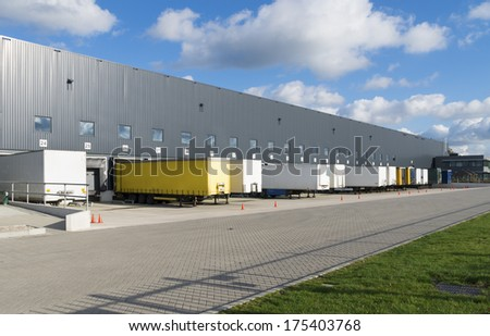 exterior of a large warehouse with loading docks and several trailers in front - stock photo
