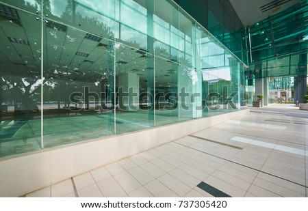 Exterior Of A Modern Steel And Green Glass Office Building With Empty  Walkway. Panoramic And
