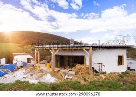 Exterior of an unfinished, ecological house and building area - stock photo