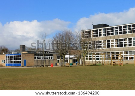 Exterior of modern school building with playing field in foreground. - stock photo