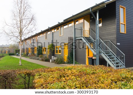 exterior of newly build townhomes with yellow doors and windows - stock photo