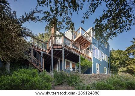Exterior of remodeled traditional craftsman home with porch surrounded by trees.  - stock photo