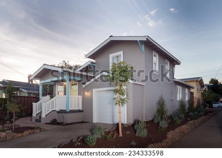 Exterior of remodeled traditional quaint coastal style home with porch on the West Coast at twilight. - stock photo