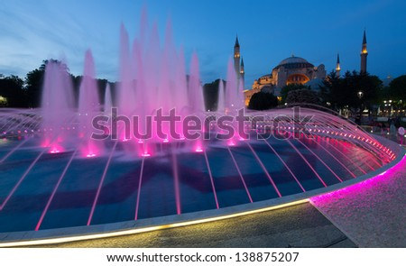 Exterior of the historical  Hagia Sofia in Istanbul, Turkey, at dusk, behind a colorful lit fountain in the park on the square in front of this historic building