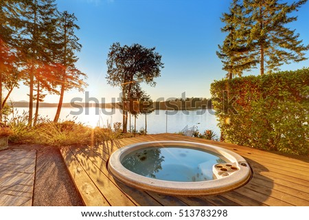 exterior of waterfront house with jacuzzi at the back yard and perfect water view at sunset