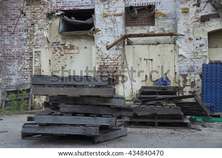 Exterior ruins of an abandoned warehouse with brick paint peeling walls, wooden and plastic crates, pipes, and steel door. - stock photo