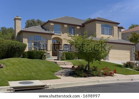 Exterior shot of a nicely landscaped two-story stucco home. - stock photo