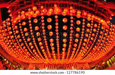 Exterior shot of a temple with a fisheye view of red lanterns. - stock photo