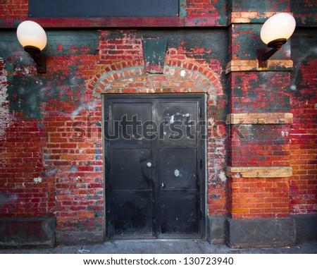 Exterior steel door on brick building exterior - stock photo