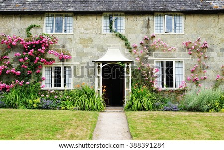 Exterior View and Garden Lawn of a Picturesque Old Rural English Cottage - stock photo