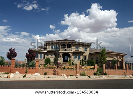 exterior view of a nice mediterranean style home from the paved street - stock photo