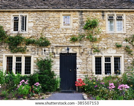 Exterior View of an Beautiful Old English House Surrounded with Flowers and Plants