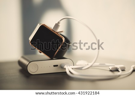 External battery, portable power bank, charging modern smart watch with power through usb cable. Fading film colors - stock photo