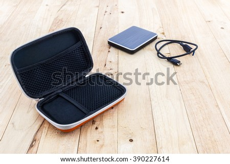 External hard drive carrying case. Bags for external hard drive on a wood background. - stock photo