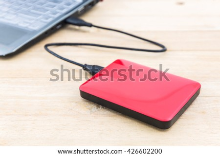 External hard drive for backup on wood background. - stock photo