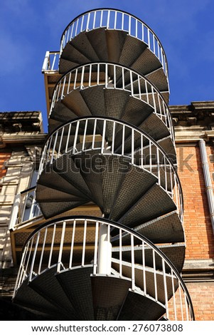 External metal spiral staircase fire escape in sunlight