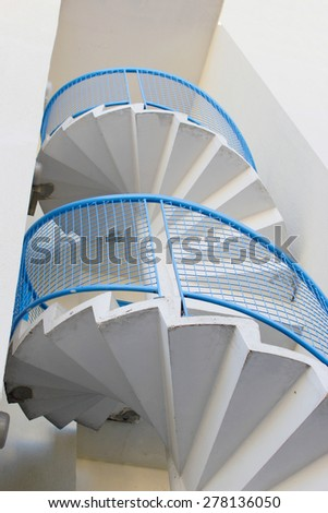 External metal spiral staircase fire escape in sunlight - stock photo