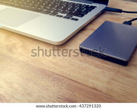 External or portable hard drive, hard disk (HDD) or solid state drive (SSD) connected to laptop computer for transfer or backup data on wooden texture office desktop with copy space, Vintage Filter - stock photo