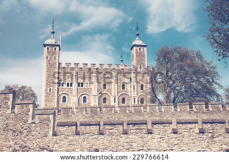 External stone facade of the iconic historical Tower of London , London , UK, a popular tourist destination and landmark against a blue sky