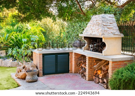 External Wood oven with burning fire and firewood - stock photo