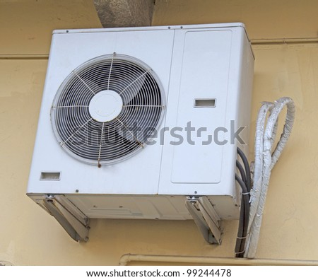 Externe engine of an air conditioner pending from wall - stock photo