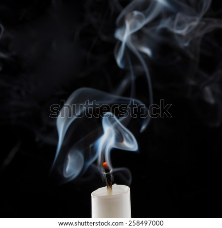 Extinguished candle with smoke (Metaphor of the death) - stock photo