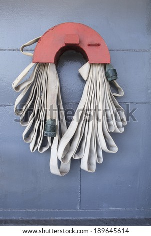 extinguishers tube line hanging on metal wall of military war ship use for safety object topic - stock photo