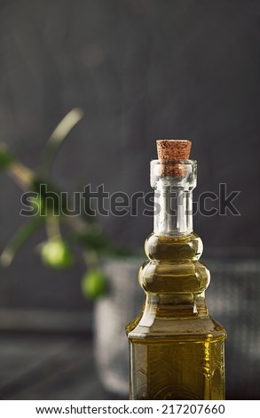 Extra virgin healthy Olive oil with fresh olives on dark wooden background
