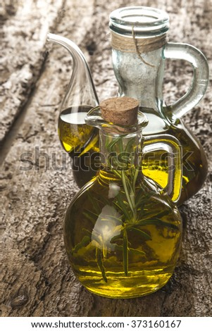 Extra virgin olive oil flavored with fresh rosemary on old wooden table