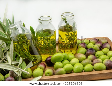 Extra virgin olive oil surrounded by freshly harvested olives
