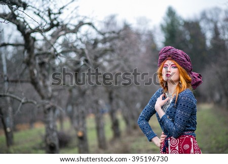 Extravagant beautiful young woman with red hair in a turban in parti-colored dress with elegant patterns posing in winter cold park among trees bent