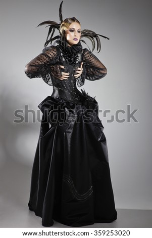 Extravagant lady posing in a black dress with a corset, decorated with tulle and black feathers