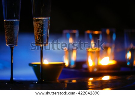 Extravagant, private romantic candlelit champagne glasses with a jacuzzi in the background. Love, celebration, relax, romance, luxurious vacation, wellness spa concept.  - stock photo