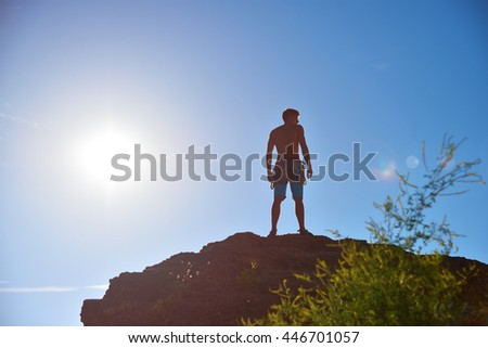 Extreme Climber On A Rock And Sun In Sky
