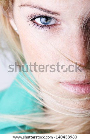 Extreme close-up beauty face portrait of a sexy woman with blue eyes and blond hairs floating with the wind looking at the camera - stock photo
