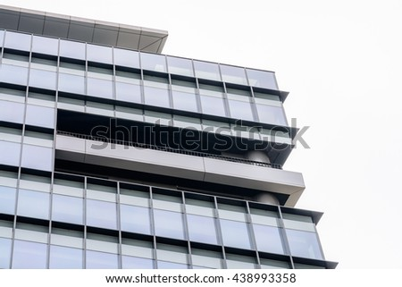 Extreme close up building windows. Low angle view of modern commercial office building with vertical windows, architectural exterior against white sky. - stock photo
