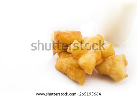 extreme close-up deep-fried doughstick and milk isolated on white background, soft focus