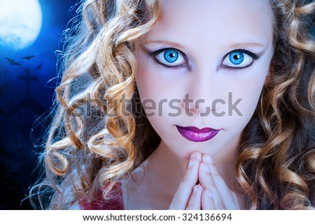 Extreme close up facial portrait of young Girl with big blue eyes. Beauty cosmetic make up on preteen with graveyard at full moon in background. - stock photo