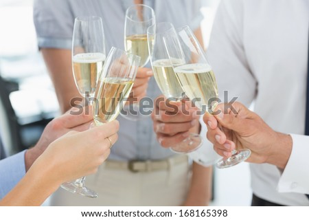 Extreme close-up hands toasting with champagne - stock photo