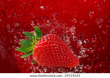 Extreme close-up image of a strawberry splashing into water - stock photo