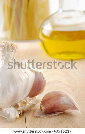 Extreme close-up image of garlic with oil and spaghetti in background