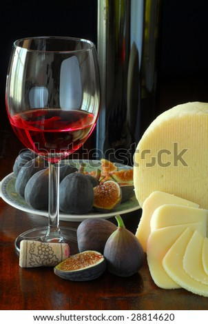 Extreme close-up image of red wine, figs and cheese