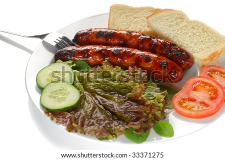 Extreme close-up image sausages served with bread, tomatoes and lettuce