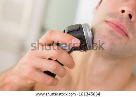 Extreme Close up of a handsome young man shaving with electric razor - stock photo
