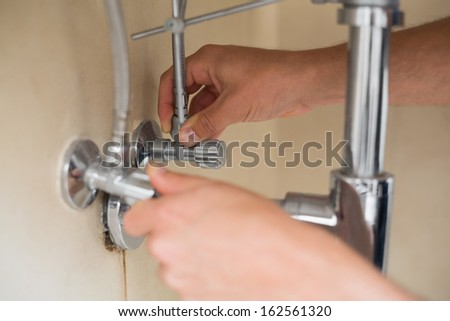 Extreme Close up of a plumber's hands and washbasin drain at bathroom - stock photo