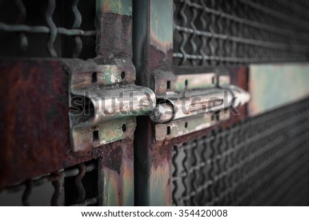 Extreme close-up of a rusty latch, left open.