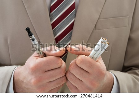 Extreme Close-up Of Businessperson Hand Holding Electronic Cigarette - stock photo