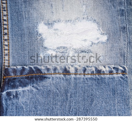 Extreme Close Up of Distressed Blue Jeans - Detail of Frayed Rip in Faded Demin Pant Leg Folded with Hem - stock photo